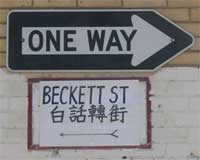 a one-way sign, beneath which is a hand-lettered sign reading BECKETT ST 白話轉街