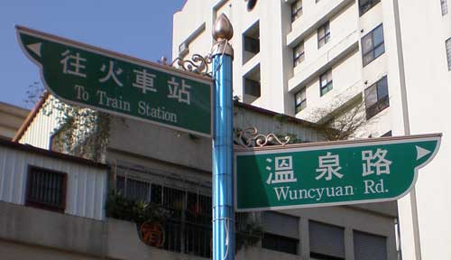 two steet signs atop one pole: one reading 'To Train Station', the other 'Wuncyuan Rd'