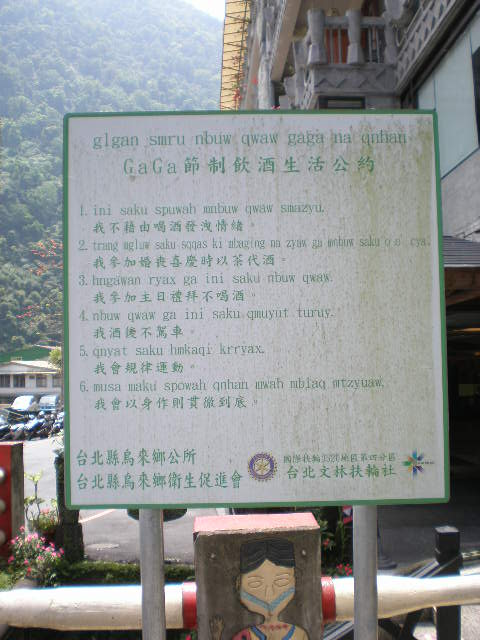 The top line reads 'glgan smru nbuw qwaw gaga na qnhan'. It's followed by 6 numbered points in romanized Atayal and then Mandarin in Chinese characters. Finally, it's identified as being from the local government as well as the Rotary Association and other groups.