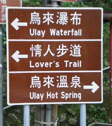 three brown (culture) signs with 'Ulay Waterfall', 'Lover's Trail', and 'Ulay Hot Spring', along with their respective Chinese characters