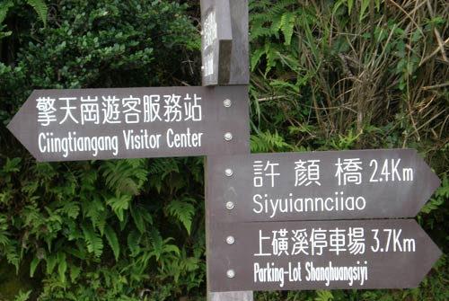 wooden directional signs reading '???????? Ciingtiangang Visitor Center / ??? Siyuiannciiao / ?????? Parking-Lot Shanghuangsiyi'