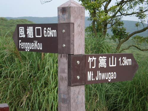 wooden directional signs reading '風櫃口 FenggueiKou' and '竹篙山 Mt.Jhwugao'