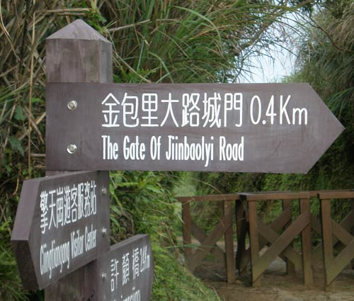 wooden directional sign reading '金包里大路城門 The Gate Of Jiinbaolyi Road'
