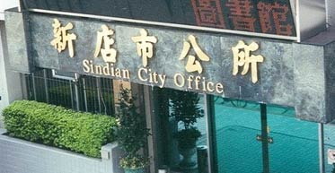 photo of the front of Xindian City Hall, across the street from the MRT station. The sign reads 'Sindian City Office'