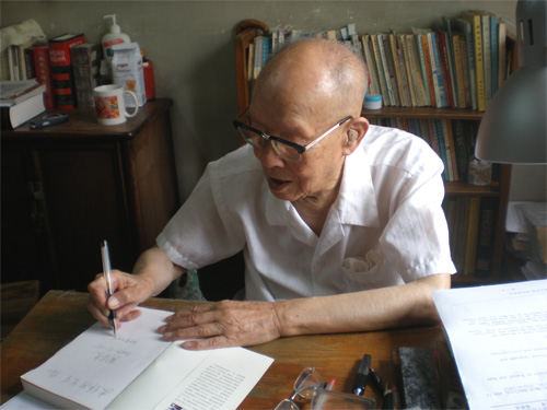 Hanyu Pinyin creator Zhou Youguang (???) at his desk, autographing a book