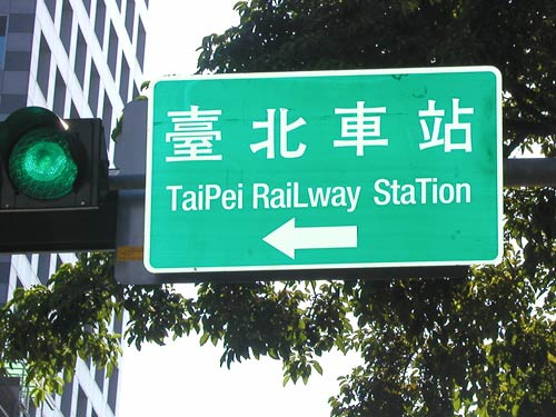 directional sign reading 'TaiPei RaiLway StaTion' (with a capital P in Taipei, a capital L in Railway and the second T capitalized in Station)