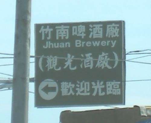 directional sign above the highway, reading 'Jhuan Brewery'