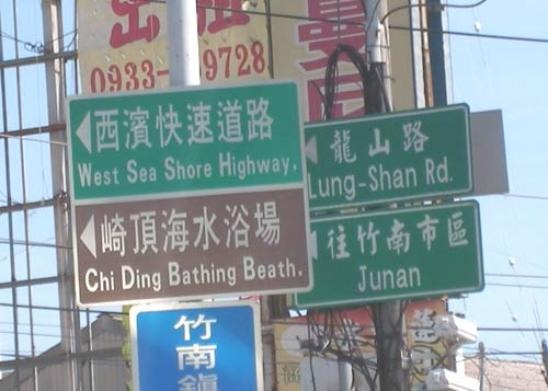 signs reading 'Junan', 'West Sea Shore Highway.', 'Lung-Shan Rd.', and 'Chi Ding Bathing Beath.'