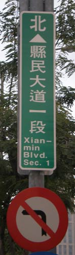 Xianmin Blvd. Sec. 1 (This is a vertical sign, too narrow for &#039;Xianmin&#039; on one line, so it&#039;s hyphenated, with &#039;min&#039; on the second line)