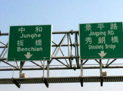 two large directional signs above a road across a bridge, as described in this post