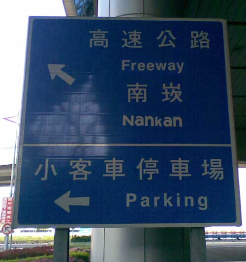a directional sign pointing the way to Nankan -- but 'Nankan' is written with all letters the same height (i.e., the capital 'N' is reduced to the height of the letter 'a' and the 'k' is similarly shrunken)