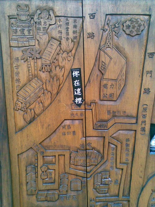 bas relief wood carving of area roads, with some buildings indicated