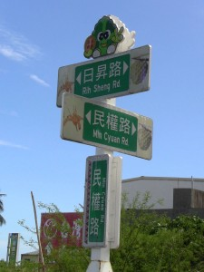 street signs reading ??? Rih Sheng Rd. / ??? Min Cyuan Rd.