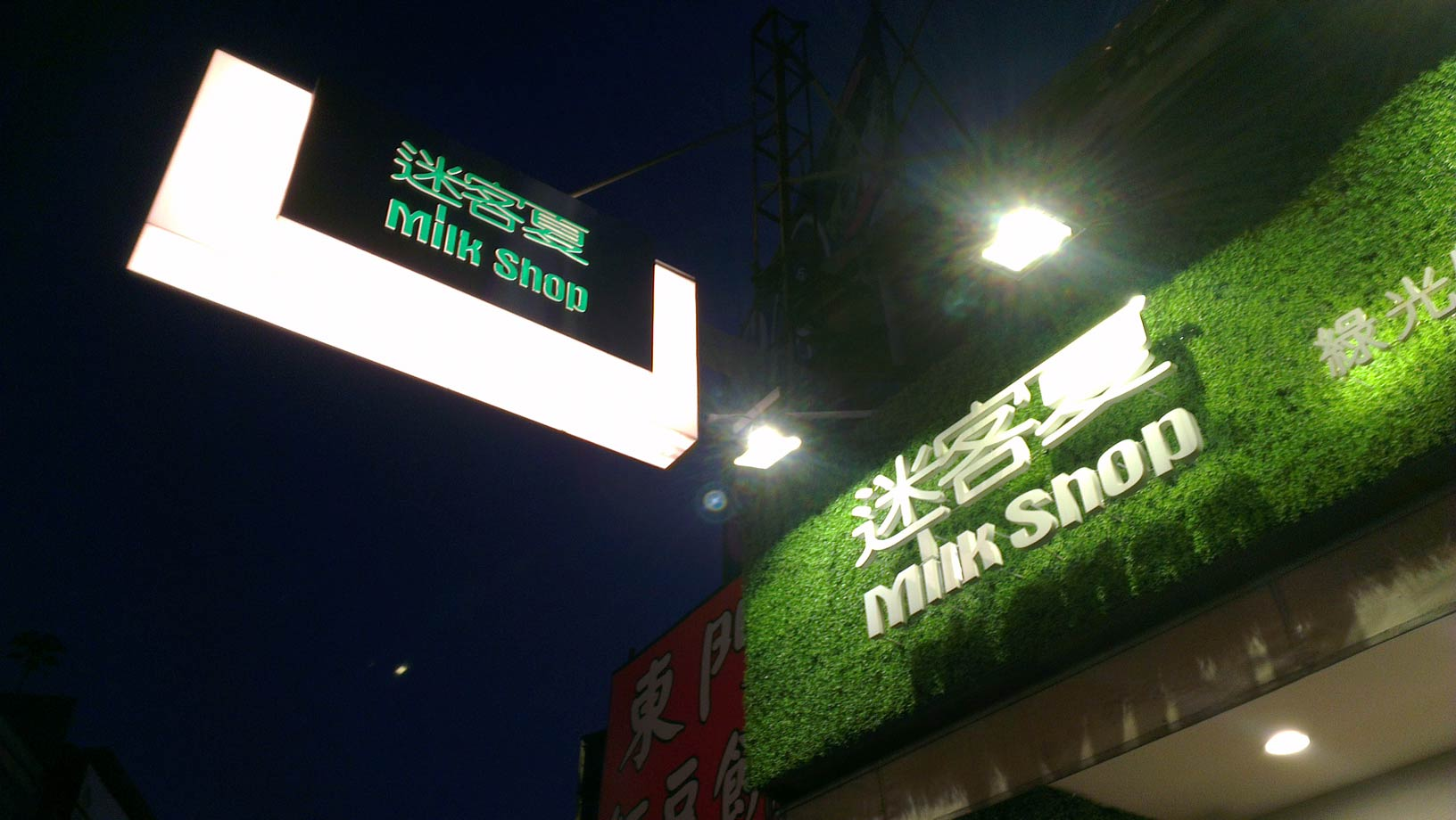 sign for a drinks store, labeled 'milk shop' in English and 'mi ke xia' in Chinese characters